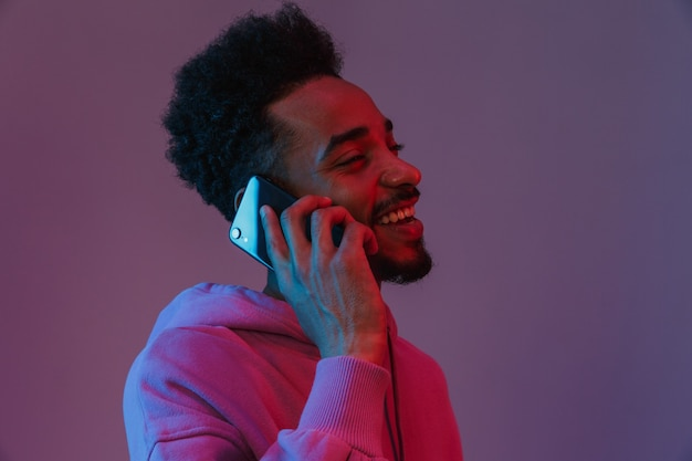 Portrait of unshaved african american man in colorful hoodie talking on cellphone isolated over violet wall