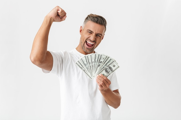 Portrait of unshaved man 30s wearing casual t-shirt celebrating while holding bunch of money banknotes isolated on white