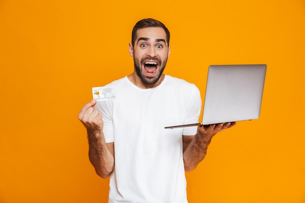 Portrait of unshaved man 30s in white t-shirt holding silver laptop and credit card, isolated