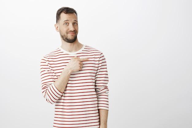 Ritratto di uomo attraente esitante incerto con la barba, che punta a destra con il dito indice con un'espressione scontenta e non impressionata