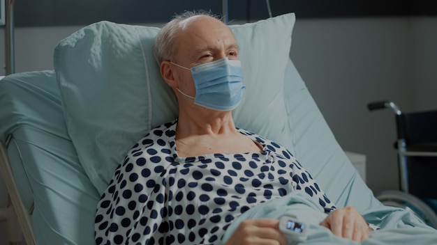 Portrait of unwell patient in hospital ward bed sitting with oximeter and face mask at intensive car...