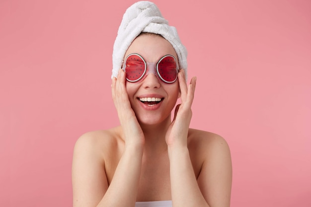 Portrait up of cheerful young cute lady after spa with a towel on her head, with mask for eyes, feels so happy, touches cheeks and broadly smiles, stands.