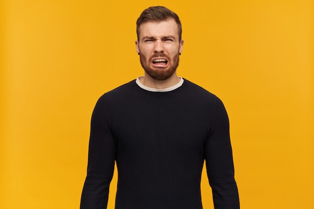 Portrait of upset, crying male with brunette hair and bristle. has piercing. wearing black sweater. emotion concept.  isolated over yellow wall