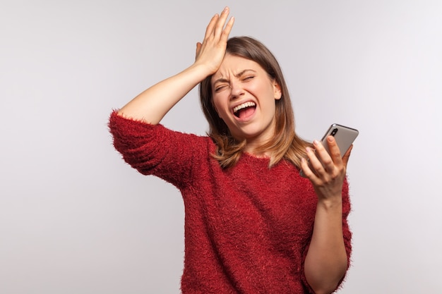 Portrait of upset depressed woman standing with facepalm gesture and holding mobile phone