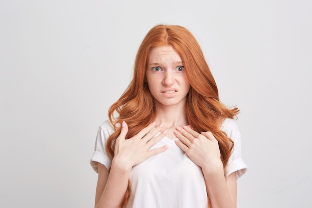 Portrait of upset depressed young woman with red wavy long hair and freckles wears t shirt feels worried and unhappy isolated over white wall