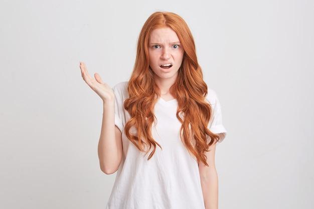 Ritratto di giovane donna depressa sconvolta con capelli lunghi ondulati rossi e lentiggini indossa maglietta si sente preoccupato e infelice isolato sopra il muro bianco