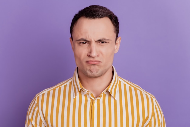 Portrait of upset disgusted guy grimace look camera frowning on purple background