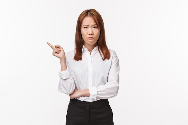 Portrait of upset and distressed asian female entrepreneur, sulking disappointed pointing finger left at something bad, feel let down and disturbed, standing unamused white wall