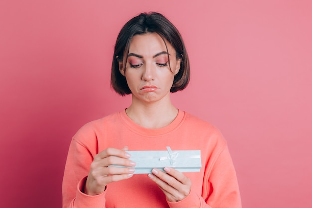 Portrait of upset frustrated girl opening gift box isolated on pink background