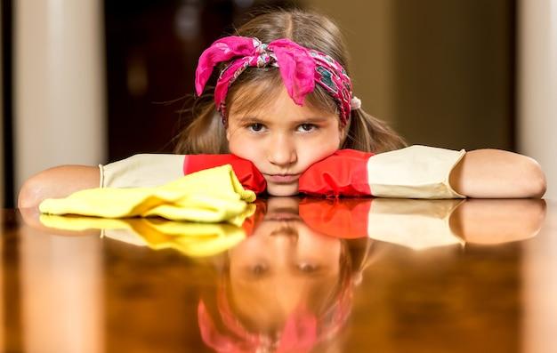 Portrait of upset girl in red rubber gloves polishing wooden table