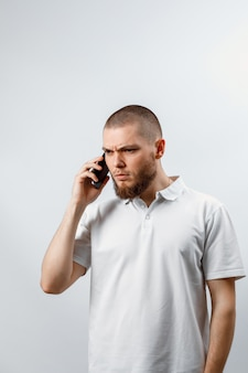 Portrait of an upset handsome bearded man in a white t-shirt talking on smartphone