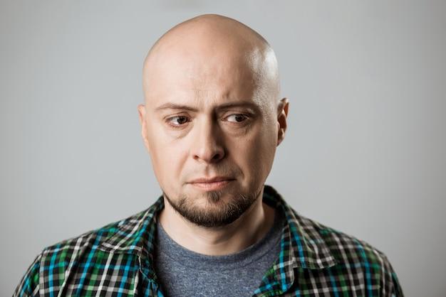 Portrait of upset handsome man thinking over beige wall