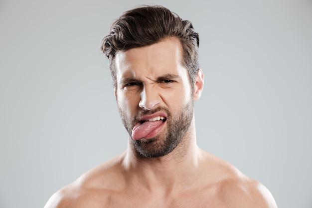 Ritratto di un uomo barbuto nudo irritato turbato che mostra lingua