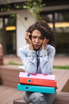 Portrait of upset lady sitting on bench with colorful folders and sadly