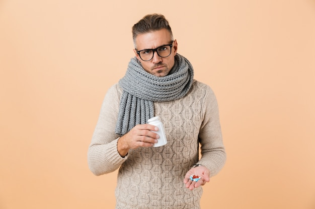 Portrait of an upset man dressed in sweater and scarf standing isolated over beige wall, showing pills capsules