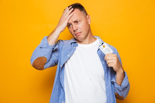 Portrait of an upset middle aged man holding credit card