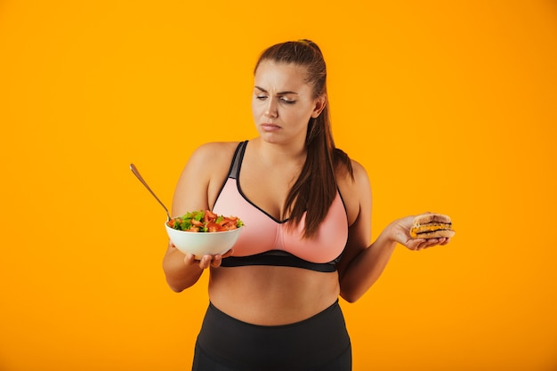 Portrait of an upset overweight fitness woman wearing sports clothing standing isolated over yellow wall, holding bowl with salad and a burger