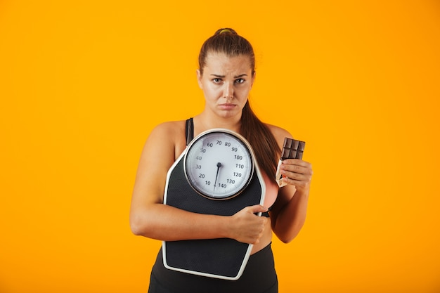 Portrait of an upset overweight young woman wearing sport clothing standing isolated over yellow wall, holding chocolate bar and scales