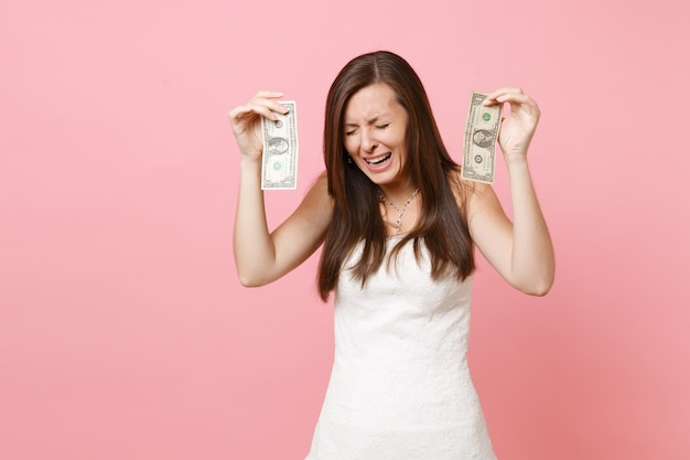Portrait of upset sad woman in white dress crying and holding one dollar bills