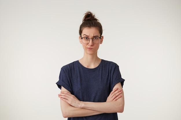 Ritratto di una donna insoddisfatta sconvolta in piedi con le braccia conserte e rigorosamente guardando attraverso gli occhiali