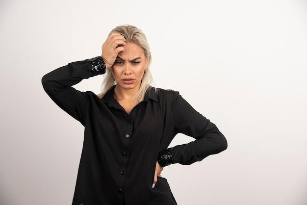 Ritratto di donna sconvolta in camicia nera in posa su sfondo bianco. foto di alta qualità