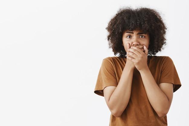 Ritratto di sconvolto preoccupato giovane di carnagione scura femmina con acconciatura afro che copre la bocca con entrambi i palmi accigliato scusa per aver detto parole scortesi