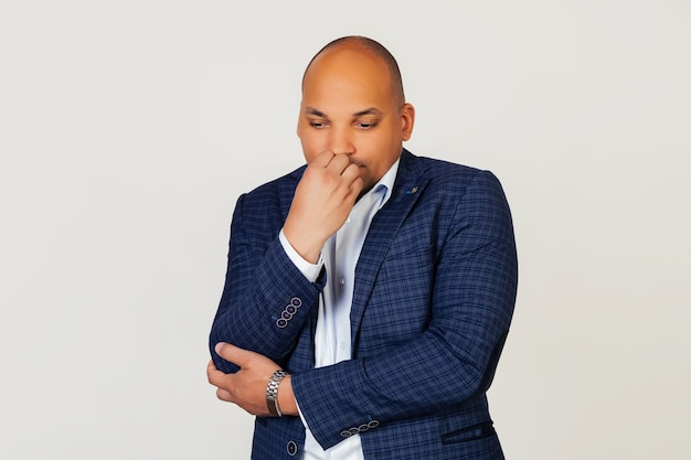 Portrait of an upset young african american businessman guy, looks tense and nervous with hands on lips, biting his nails. anxiety problem.