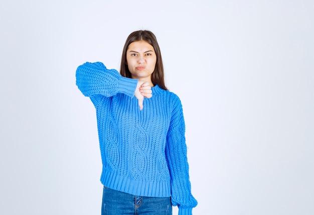 Ritratto di un modello di ragazza sconvolta che mostra un pollice verso il basso.