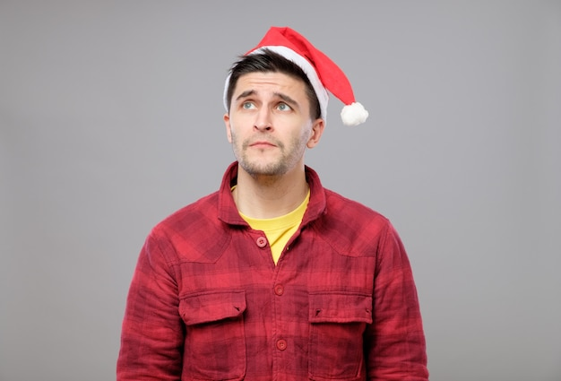 Portrait of upset young man in red santa claus hat