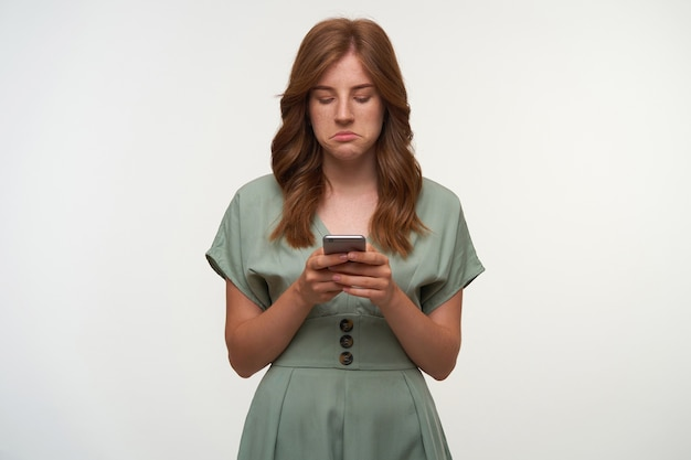 Portrait of upset young pretty female in vintage dress with smartphones in hands, looking at screen with sad face, reading bad news, isolated