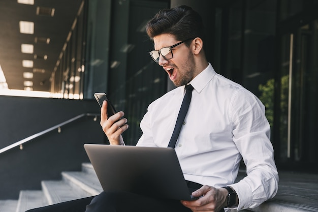 Portrait of uptight businessman dressed in formal suit sitting outside glass building with laptop, and using smartphone