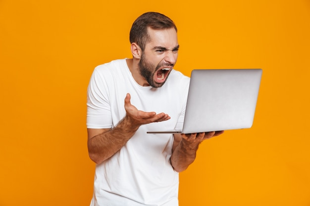 Portrait of uptight man 30s in white t-shirt screaming and holding silver laptop, isolated