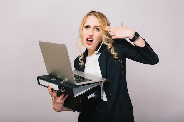 ノートパソコン、フォルダー、ボックスを保持しているフォーマルなスーツの肖像画非常に忙しい若い実業家、電話で話している、見ています。仕事、仕事、管理、秘書、会議、職業