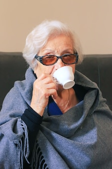 Portrait of a very elderly woman drinking coffee. positive ninety year old grandmother.