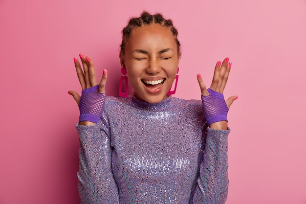 Portrait of very happy amused woman has dark skin, raises hands, shows sport gloves, wears glittering purple jumper, laughs positively, hears something hilarious, models over pastel rosy wall