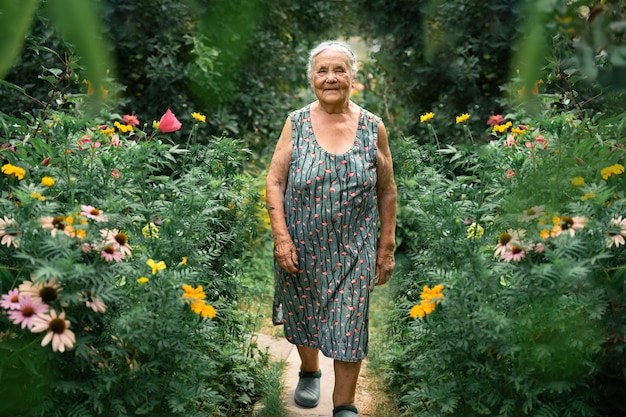 Portrait of a very old woman walking in her garden  with flowers in summer. grandparents day. hobbies for the elderly concept.