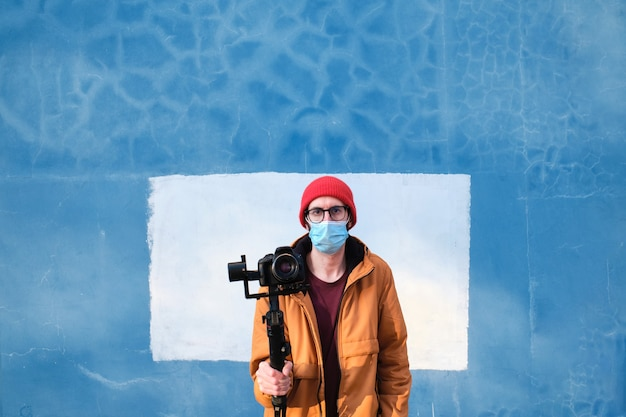 Portrait of a videographer wearing a protective face mask with a dslr camera on a motorized gimbal