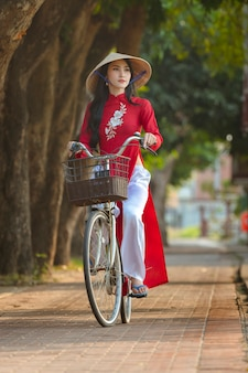 Portrait of vietnamese girl traditional red dress,beautiful young asian woman wearing vietnam with bicycle