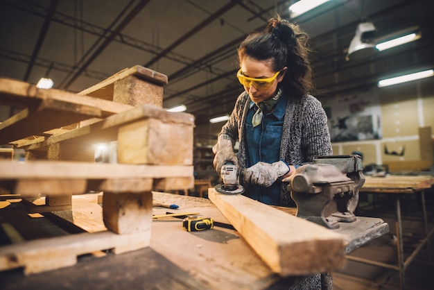 Portrait view of hardworking professional female carpenter working with sandpaper and choosing wood in the workshop