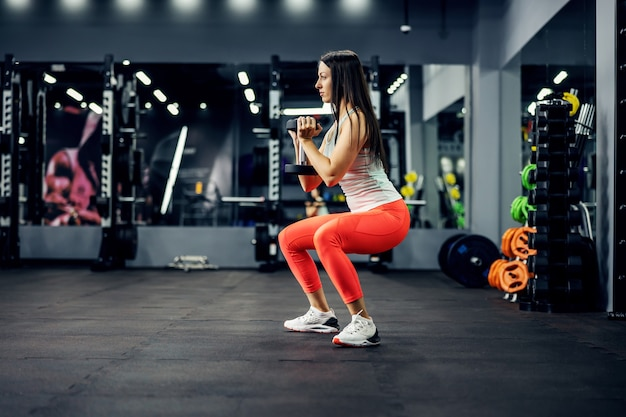Portrait view of a muscular young brunette woman in sports clothing doing deep squats with the dumbbell in a brutal interior of the fitness center