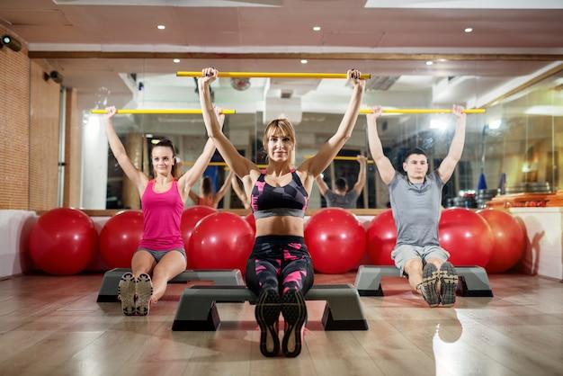 Взгляд портрета группы фитнеса красивой здоровой формы активной sporty сидя на steppers и держа бары поднятые над головой в передней серии шариков и зеркала фитнеса в спортзале.