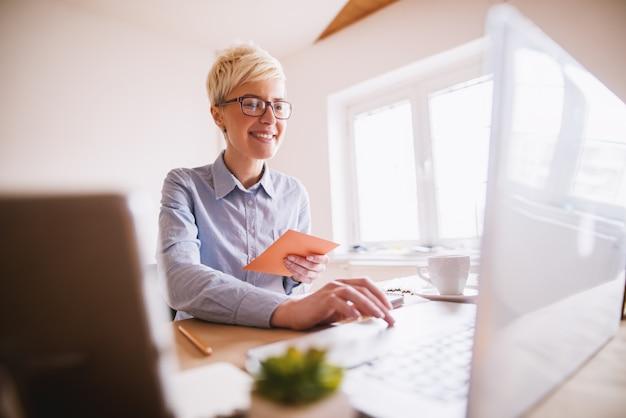 明るいオフィスでラップトップに取り組んで美しい笑顔のファッション・デザイナーの縦向きビュー。