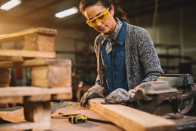 Взгляд портрета счастливого привлекательного профессионального женского работника плотника смотря и выбирая древесину в мастерской