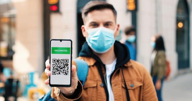 카메라를 보고 백신 여권을 보여주는 보호 마스크를 쓴 진지한 남자의 초상화...