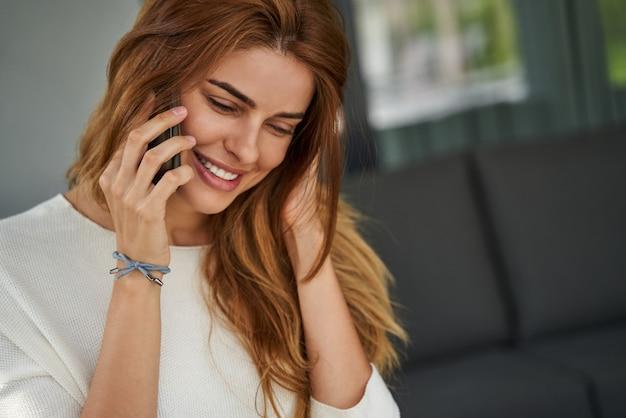 그녀의 테라스에 서서 누군가와 전화 통화를 하는 쾌활한 노인 여성의 초상화. 스톡 사진