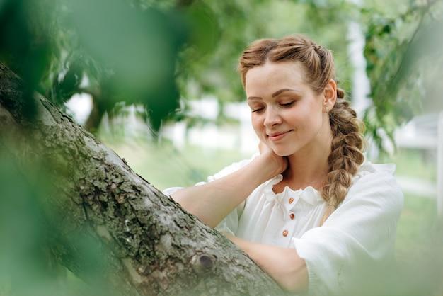여성 모델의 초상화는 푸른 잔디가 있는 들판에 서서 신선한 공기를 마시며 눈을 감았다. 갈색 머리를 가진 아름 다운 젊은 여자. 자연 개념
