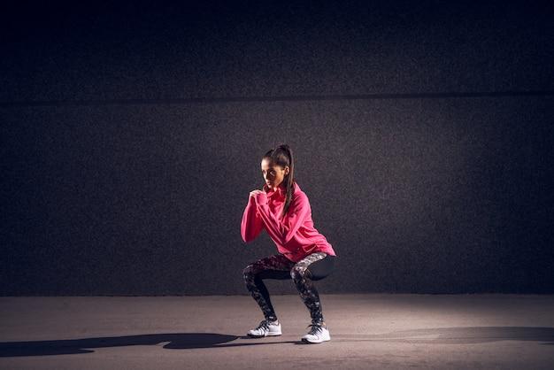 若いセクシーな魅力的な健康的なフィットネススポーティなアクティブなスリムな女の子の肖像画ビュースポーツウェア身をかがめると、路上で夜に灰色の壁の前で一緒に手を押しながらスクワットをやっています。