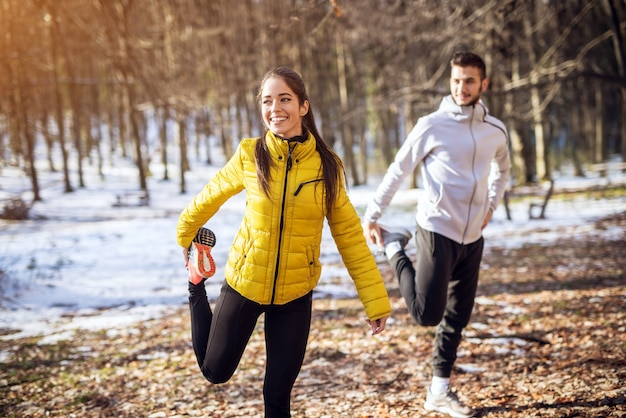 Portrait view of young happy attractive beautiful smiling fitness sporty couple in winter sportswear warming in the snowy forest.