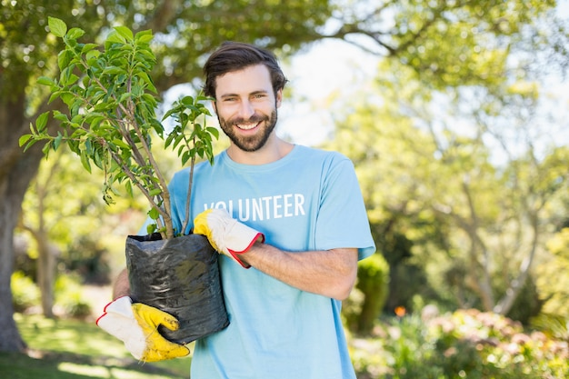 Portrait of volunteer man holding plant