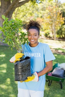 Portrait of volunteer woman holding plant